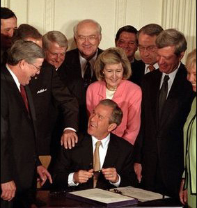 U.S. President  signs a bill into law at a public ceremony. As Head of State, the President's signature is required on all laws absent a  of congress.