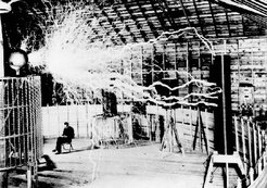 "Publicity photo of Tesla sitting in his laboratory in Colorado Springs with his ""magnifying transmitter"" generating millions of volts of electricity.  The arcs are about 7 meters (22 ft) long. (Tesla's notes identify this as a .)"