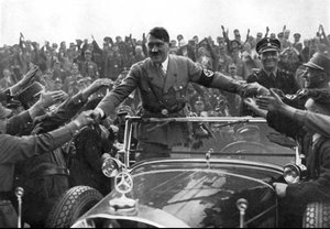 Adolf Hitler greeting supporters from aboard a parade vehicle