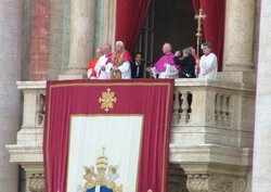 With a tapestry bearing the coat of arms of John Paul II hanging over the balcony, Benedict XVI is introduced to the crowd gathered in Saint Peter's Square.